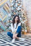 Рождество красивейший усмехаться девушки сидит над предпосылкой светов рождественской елки счастливое Новый Год Стоковые Фото