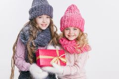 Рождество Новый Год 2 маленьких сестры держа присутствующей в одеждах зимы Розовые и серые шляпы и шарфы Семья Зима стоковые изображения rf