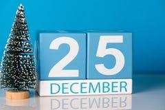 Рождество 25-ое декабря День 25 месяца в декабре, календаря с меньшей рождественской елкой на голубой предпосылке зима времени сн Стоковое Изображение RF