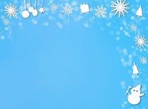 Рождество орнаментирует границу на голубой предпосылке снега Стоковая Фотография