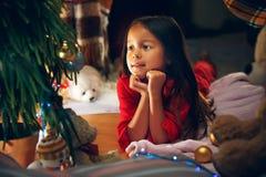 Рождество, праздники и концепция детства - счастливая девушка в красных одеждах украшая естественную ель стоковые фотографии rf