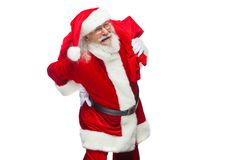Рождество Санта Клаус страдает от боли в спине и держит красную сумку с подарками на его назад Изолировано на белизне стоковые фотографии rf
