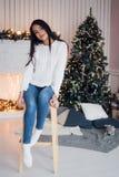 рождество торжества веселое Красивая изумительная молодая женщина в голубые джинсы и белое sweather сидя около рождества Стоковые Изображения RF