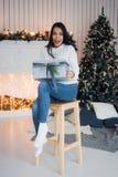 рождество торжества веселое Красивая изумительная молодая женщина в голубые джинсы и белое sweather сидя около рождества Стоковое фото RF
