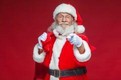 Рождество Усмехаясь Санта Клаус в белых перчатках с сумкой подарков за им пункты его указательный палец в камеру стоковые фотографии rf