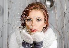 Рождество, x-mas, люди, концепция счастья - счастливая девушка в зиме одевает дуть на ладонях Стоковые Изображения RF