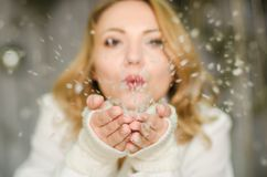 Рождество, x-mas, люди, концепция счастья - счастливая девушка в зиме одевает дуть на ладонях Стоковое фото RF