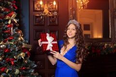 Рождественская вечеринка, женщина зимних отдыхов с подарочной коробкой Новый Год девушки рождественская елка в внутренней предпос Стоковое Изображение