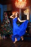 Рождественская вечеринка, женщина зимних отдыхов с подарочной коробкой Новый Год девушки рождественская елка в внутренней предпос Стоковое фото RF