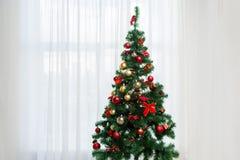 Рождественская елка в живущей комнате над занавесом окна стоковые изображения
