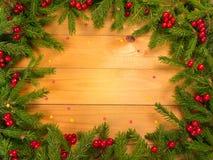 Рождественская елка и красная рамка ягод на деревянных wi предпосылки Стоковые Фото