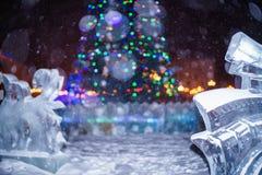 Рождественская елка окруженная ледяной скульптурой во время снежной ночи Стоковое Фото