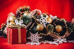 Рождественская открытка при ветвь ели украшенная с золотыми безделушками, гирляндами и снежинками года сбора винограда на красной Стоковые Фотографии RF