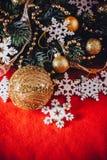 Рождественская открытка при ветвь ели украшенная с золотыми безделушками, гирляндами и снежинками года сбора винограда на красной Стоковые Изображения RF
