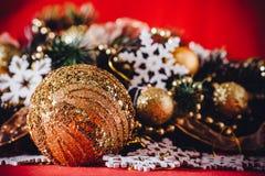 Рождественская открытка при ветвь ели украшенная с золотыми безделушками, гирляндами и снежинками года сбора винограда на красной Стоковое Фото