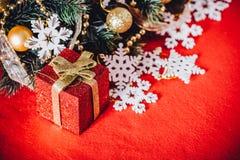 Рождественская открытка при ветвь ели украшенная с золотыми безделушками, гирляндами и снежинками года сбора винограда на красной Стоковое Изображение