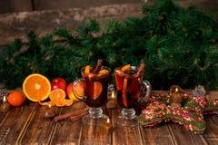 Рождество обдумывало вино с плодоовощами и специями на деревянном столе Украшения Xmas в предпосылке стекла 2 Питье r зимы грея Стоковые Изображения RF