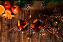 Рождество обдумывало вино с плодоовощами и специями на деревянном столе Украшения Xmas в предпосылке стекла 2 Питье r зимы грея Стоковые Фото