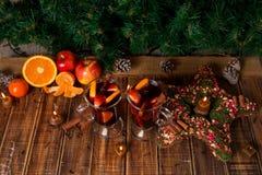 Рождество обдумывало вино с плодоовощами и специями на деревянном столе Украшения Xmas в предпосылке стекла 2 Питье r зимы грея Стоковые Изображения