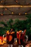 Рождество обдумывало вино с плодоовощами и специями на деревянном столе Украшения Xmas в предпосылке стекла 2 Питье r зимы грея Стоковое Фото
