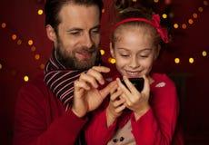 Рождество - отец и дочь играя игру на мобильном телефоне Стоковое фото RF