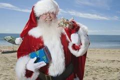 Рождество отца стоит с его мешком на пляже Стоковые Изображения RF