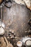 Рождество печет деревянную предпосылку с прессформами печений, мукой, инструментами кухни и ушами стоковая фотография