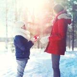Рождество, семья и концепция зимы - счастливый сын ребенка дает подарочную коробку матери в солнечной зиме Стоковая Фотография
