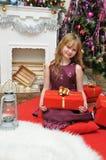 рождество счастливое Счастливая девушка с подарками камином Стоковое фото RF