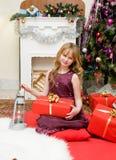 рождество счастливое Счастливая девушка с подарками камином Стоковые Изображения
