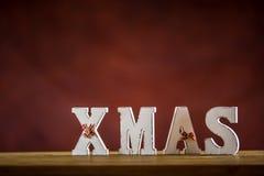 Рождество Слово Xmas сделанное деревянных писем на таблице деревянной доски Хворостина ели звезды конуса сосны шариков рождества  Стоковая Фотография RF