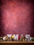 Рождество Слово Xmas сделанное деревянных писем на таблице деревянной доски Хворостина ели звезды конуса сосны шариков рождества  Стоковые Изображения RF