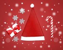 Рождество установило - красную крышку Санта Клауса, подарочную коробку, снежинки, тросточку конфеты карамельки над предпосылкой с Стоковое Изображение