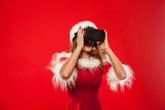 Рождество, x-mas, зима, концепция счастья - красивое молодое брюнет с длинными волосами в носить шляпы хелпера santa Стоковые Фотографии RF