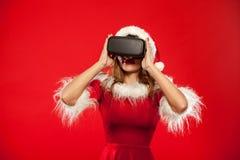 Рождество, x-mas, зима, концепция счастья - красивое молодое брюнет с длинными волосами в носить шляпы хелпера santa Стоковое фото RF