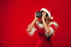 Рождество, x-mas, зима, концепция счастья - красивое молодое брюнет с длинными волосами в носить шляпы хелпера santa Стоковое Изображение RF