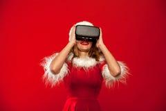 Рождество, x-mas, зима, концепция счастья - красивое молодое брюнет с длинными волосами в носить шляпы хелпера santa Стоковые Изображения
