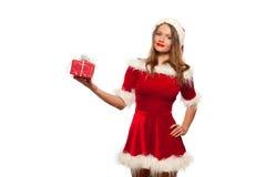 Рождество, x-mas, зима, концепция счастья - усмехаясь женщина в шляпе хелпера santa при подарочная коробка, изолированная на бели Стоковые Изображения