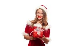 Рождество, x-mas, зима, концепция счастья - усмехаясь женщина в шляпе хелпера santa при подарочная коробка, изолированная на бели Стоковая Фотография RF