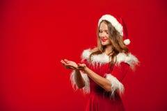 Рождество, x-mas, зима, концепция счастья - усмехаясь женщина в шляпе хелпера santa при подарочная коробка, держа руки перед Стоковые Изображения