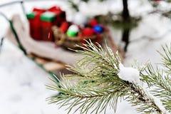 Розвальни, одеяло, корзина с игрушками и подарочные коробки в снежном для Стоковые Изображения