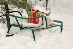 Розвальни, одеяло, корзина с игрушками и подарочные коробки в снежном для Стоковое Фото