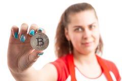 Розничный торговец молодой женщины или символ bitcoin продаж ассистентский держа стоковые фото