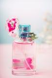 Розовая бутылка флористического дух с цветками, естественным косметическим продуктом или концепцией красоты на пастельной предпос Стоковое фото RF