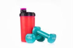 Розовая бутылка blender протеина с парой голубых гантелей фитнеса Концепция студии фитнеса Стоковые Фотографии RF