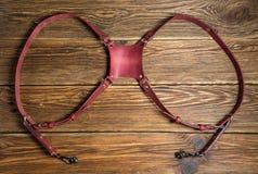 Розовая двойная проводка камеры, проводка ремня мульти-камеры, кожаный ремень камеры на коричневой деревянной предпосылке Стоковые Изображения RF