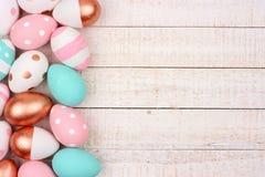 Розовая граница стороны золота, пинка, бирюзы и пасхального яйца белизны на белой древесине Стоковая Фотография RF