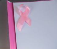Розовая лента на куске бумаги для того чтобы поднять рак молочной железы осведомленности, космос экземпляра Стоковые Изображения RF