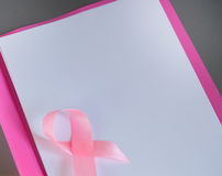 Розовая лента на куске бумаги для того чтобы поднять рак молочной железы осведомленности, космос экземпляра Стоковые Изображения