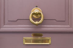 Розовая деревянная дверь с золотыми кольцом и почтовым ящиком Стоковая Фотография